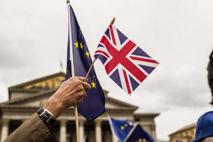 Флажки ЕС и Великобритании в руке мужчины