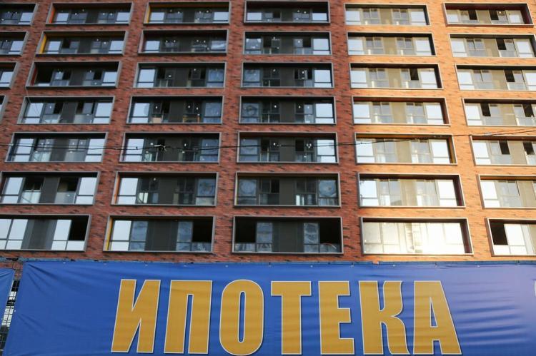 "Надпись ""Ипотека"" на фоне многоквартирного дома"