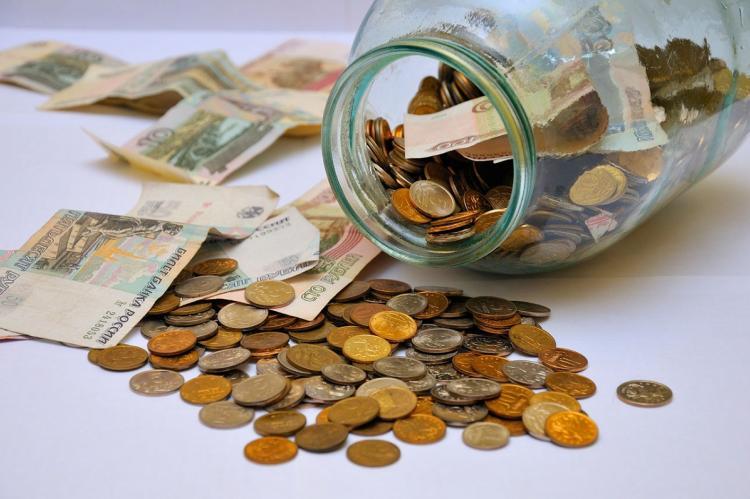 Деньги в стеклянной банке и россыпью
