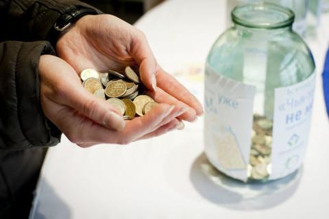 Монеты в стеклянной банке и в руках