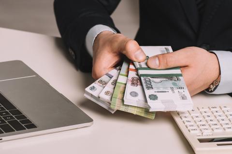 Пачки денег в руках