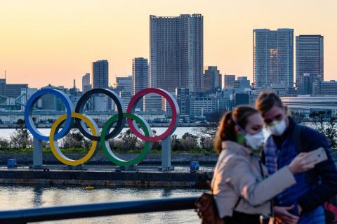 Туристы фотографируются на фоне олимпийской символики